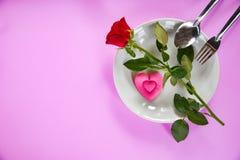 Romantische Liebesnahrung des Valentinsgrußabendessens und Liebe, die Gabellöffelrosaherz und -rosen auf Platte mit rosa Beschaff lizenzfreies stockbild