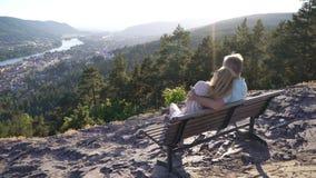 Romantische liebevolle Paare, die auf Holzbank sitzen und die Stadt und den Fluss im Tal bewundern stock video