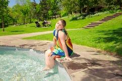 Romantische meisjezitting, die op de rand van waterpool ontspannen in openluchtpark Royalty-vrije Stock Foto's