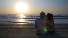 Romantische minnaars op het strand die en bij schemering dichtbij het overzees koesteren kussen stock videobeelden