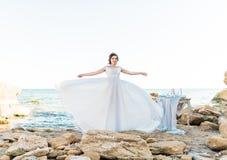Romantische mooie bruid in luxekleding het stellen op het strand Royalty-vrije Stock Afbeeldingen