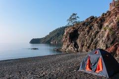 Romantische ontsnapping in een tent op een leeg strand vanaf grote hotels stock afbeelding