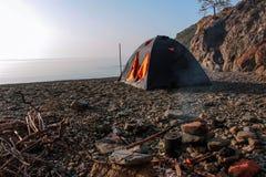 Romantische ontsnapping in een tent op een leeg strand vanaf grote hotels stock foto's