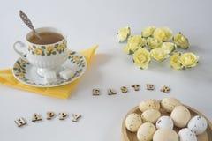 Romantische Ostern-Szene mit Eiern, hölzerne Buchstaben und gelbe Rosen, auf weißer Tabelle stockfotografie