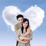 Romantische Paare über geformter Wolke des Herzens stockbild