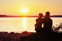 Romantische Paare auf dem Strand am bunten Sonnenunterganghintergrund lizenzfreies stockbild