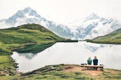 Romantische Paare auf einer Bank durch den Gebirgssee Stockfotografie