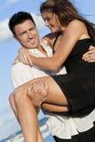 Romantische Paare auf Strand, Mann, der seine Frau trägt Lizenzfreie Stockfotos