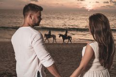 Romantische Paare auf Thstrand während des Sonnenuntergangs stockfotografie