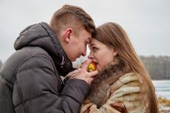 Romantische Paare in der Liebe auf Herbst- oder Winterweg mit Apfel lizenzfreie stockfotos
