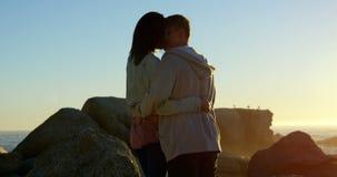 Romantische Paare, die auf dem felsigen Ufer 4k sich küssen stock footage