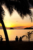 Romantische Paare, die auf einem Strand am Sonnenuntergang sitzen Lizenzfreie Stockfotos