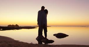 Romantische Paare, die auf felsigem Ufer 4k sich küssen stock video