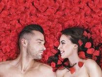 Romantische Paare, die auf rosafarbene Blumenblätter legen Lizenzfreie Stockfotos