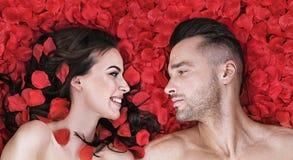 Romantische Paare, die auf rosafarbene Blumenblätter legen Stockfotografie