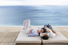 Romantische Paare, die auf Sunbeds durch Unendlichkeits-Pool sich entspannen Stockfoto