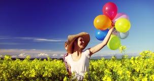 Romantische Paare, die bunte Ballone und Betrieb auf dem Senfgebiet halten stock video footage
