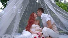 Romantische Paare, die in den Dekorationen für Heiratsfotosession am Park küssen stock video