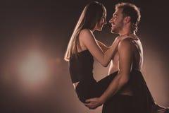 romantische Paare, die einander, auf Braun umarmen und betrachten lizenzfreie stockfotografie