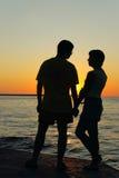 Romantische Paare, die einander auf Sonnenuntergang betrachten Lizenzfreie Stockfotografie