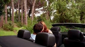 Romantische Paare, die in einem konvertierbaren Auto küssen stock footage