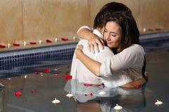 Romantische Paare, die in einem Pool mit Kerzen und den rosafarbenen Blumenblättern umarmen Stockfoto
