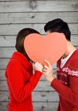 Romantische Paare, die ihr Gesicht hinter Herzen verstecken Lizenzfreie Stockbilder