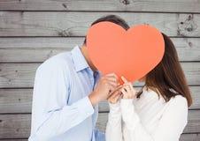 Romantische Paare, die ihr Gesicht hinter Herzen verstecken Stockbilder