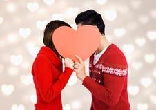 Romantische Paare, die ihr Gesicht hinter rotem Herzen verstecken Lizenzfreie Stockbilder
