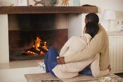 Romantische Paare, die im Aufenthaltsraum nahe bei offenem Feuer sich entspannen lizenzfreie stockfotografie