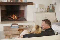 Romantische Paare, die im Aufenthaltsraum nahe bei offenem Feuer sich entspannen stockbilder