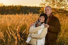 Romantische Paare, die im Landschaftsherbstsonnenuntergang umarmen Stockbilder