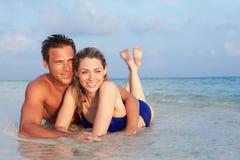 Romantische Paare, die im Meer auf tropischem Strandurlaub liegen stockbild