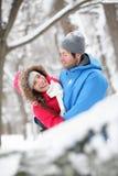 Romantische Paare, die im Schnee umarmen Lizenzfreie Stockfotografie