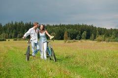 Romantische Paare, die mit altem Fahrrad in der Wiese gehen Stockfoto