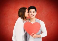 Romantische Paare, die mit Valentinsgrußherzen gegen roten Hintergrund küssen Stockfotografie