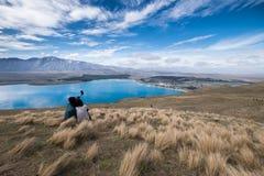 Romantische Paare, die selfie auf einem grassfield im See Tekapo, Neuseeland nehmen stockbild