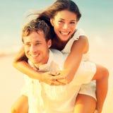 Romantische Paare, die Spaßdoppelpol auf Strand haben Lizenzfreies Stockfoto