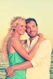 Romantische Paare, die am Strand lächeln und umfassen Stockfoto