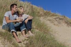 Romantische Paare, die zusammen auf einem Strand sitzen Stockbilder
