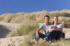 Romantische Paare, die zusammen auf einem Strand sitzen Lizenzfreies Stockfoto