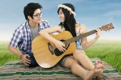 Romantische Paare, die zusammen Gitarre spielen Stockbild