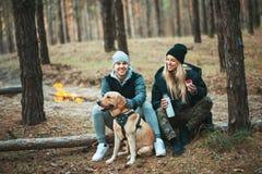 Romantische Paare mit dem Hund, der nahe Feuer, Herbstwaldhintergrund sitzt Junge Blondine und gutaussehender Mann Konzept - Fami Stockfotografie