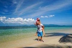 Romantische Paare mit Santa Claus Hats Have Fun auf dem Strand Feiern von Weihnachten und von neuem Jahr im heißen Land stockfotografie