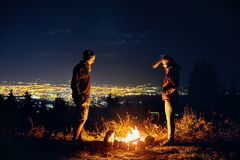 Romantische Paare nähern sich Lagerfeuer nachts lizenzfreie stockfotos
