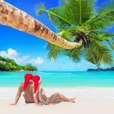Romantische Paare in roten Weihnachts-Sankt-Hüten nehmen am sandigen Inselstrand der tropischen Palme ein Sonnenbad Lizenzfreies Stockbild