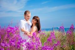 Romantische Paare unter purpurroten Blumen nähern sich blauem Meer Stockfotografie