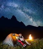 Romantische Paarliebhaber, die zum sternenklaren Himmel des Glanzes und zur Milchstraße im Kampieren nachts nahe Lagerfeuer schau Stockbild