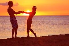 Romantische paarpret op strandzonsondergang tijdens reis Stock Foto
