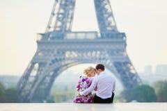 Romantische paarzitting dichtbij de toren van Eiffel in Parijs, Frankrijk stock fotografie